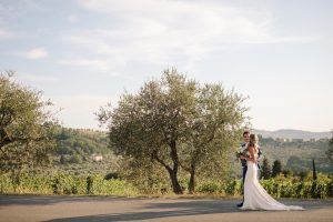 intimate catholic wedding Tuscany -  bride and groom walking in a olive groves