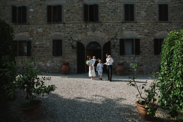 organic wedding - bride and groom walking to the ceremony with the villa background