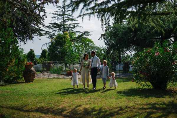 organic wedding - bride and groom and their children walking down the aisle