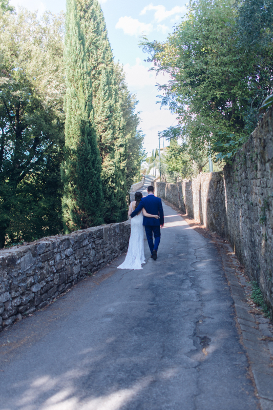 simple wedding - bride and groom walking in the back of the villa